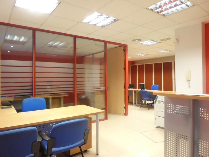 Oficina con zona de recepción, puestos para administración y despac...